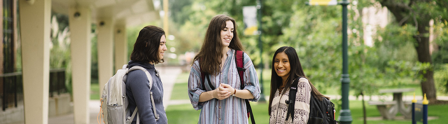 three students talk outside residence hall