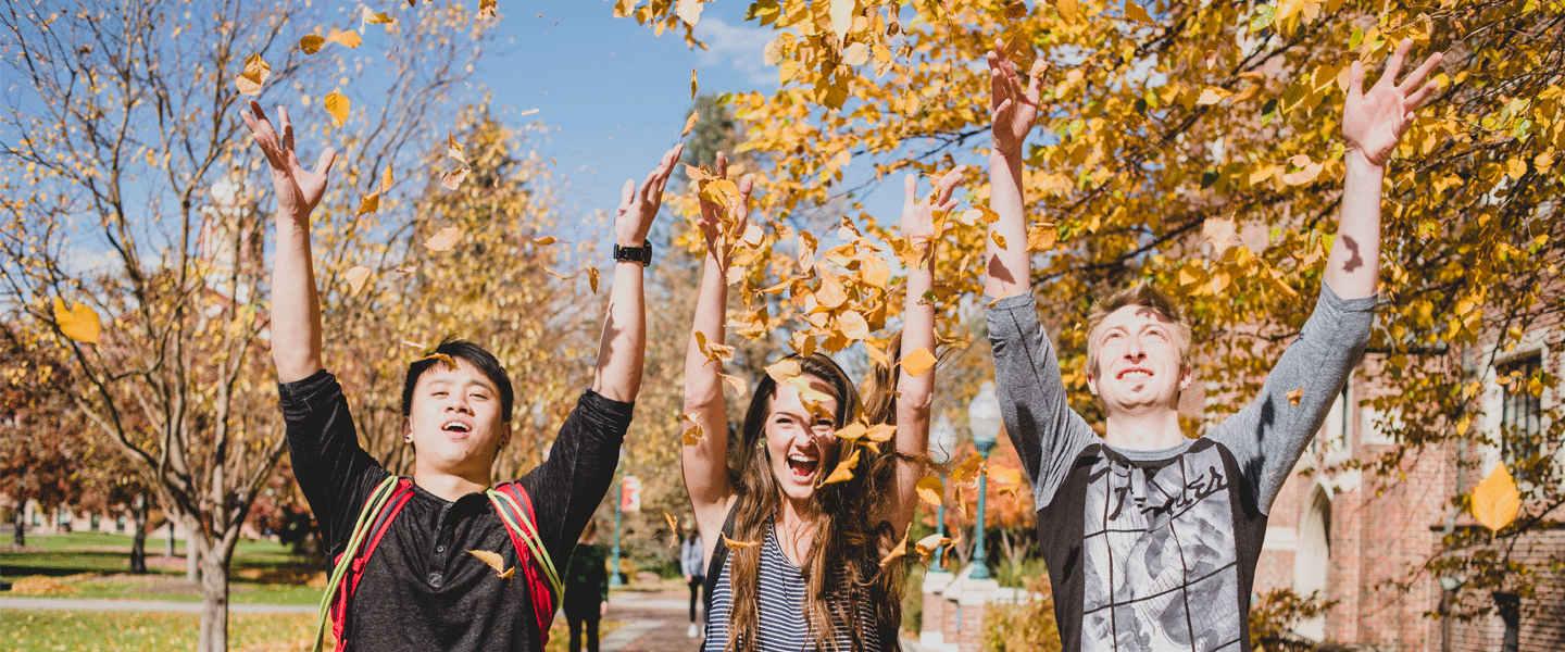 smiling students throwing leaves in air in fall