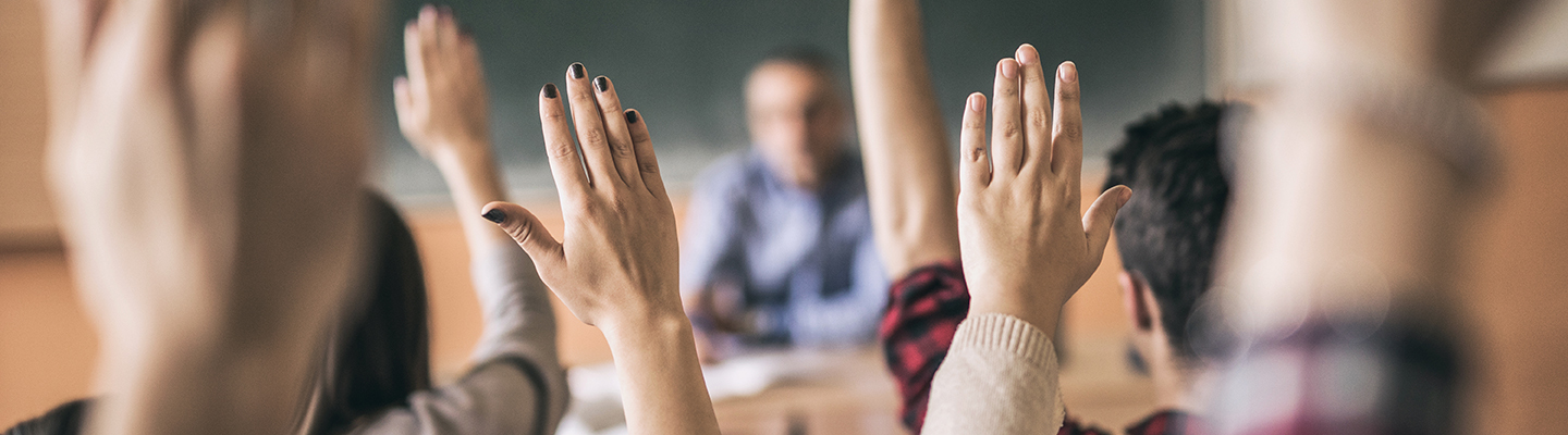 students in classroom with hands raised