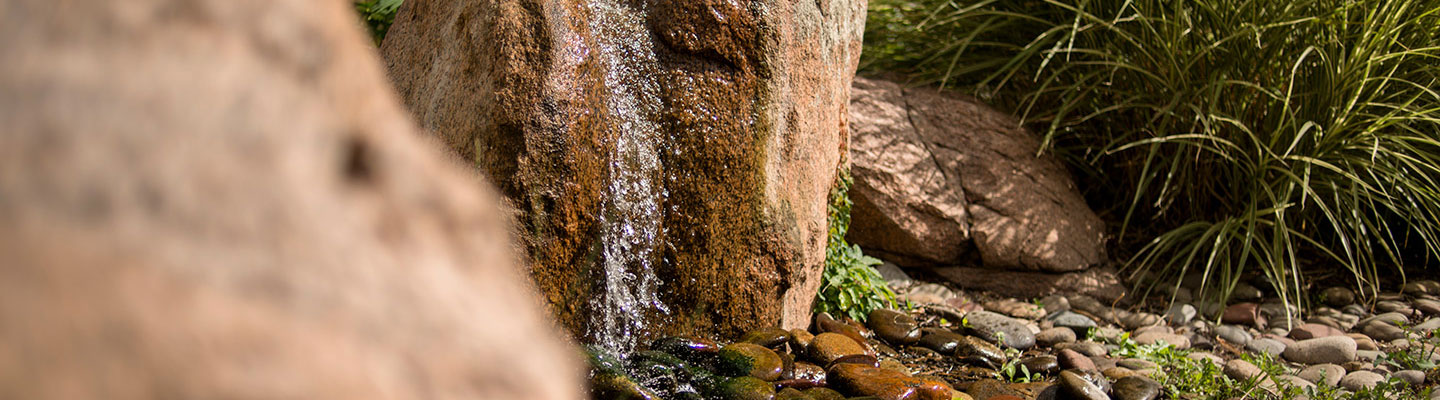 rock with water trickling down to ground