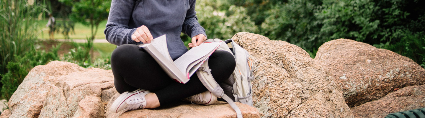 girl sits on rock studying