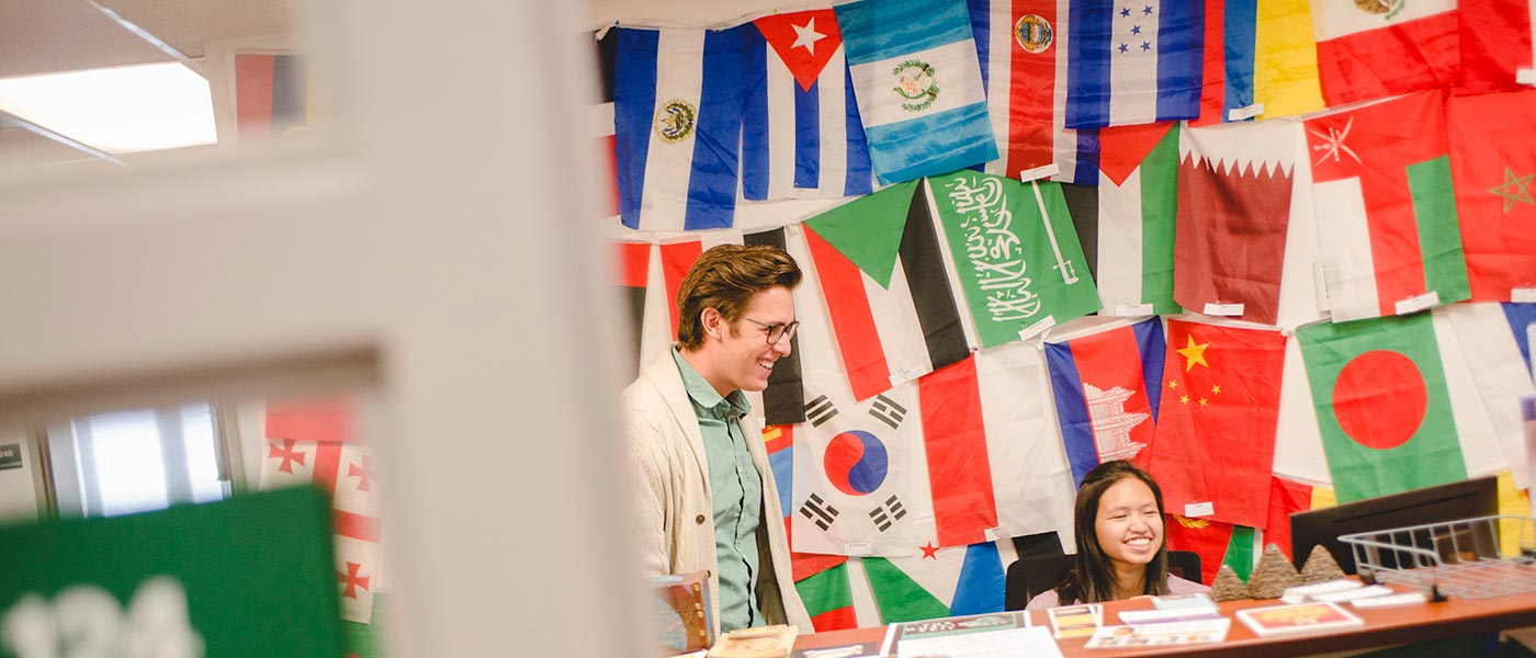 two people smile with international flags behind them