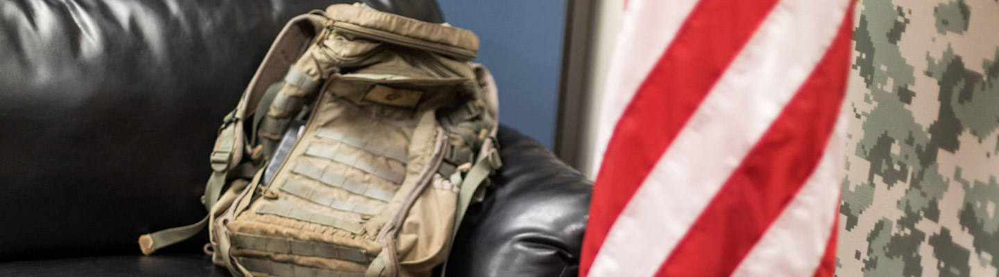 military grade backpack sits on couch by flag