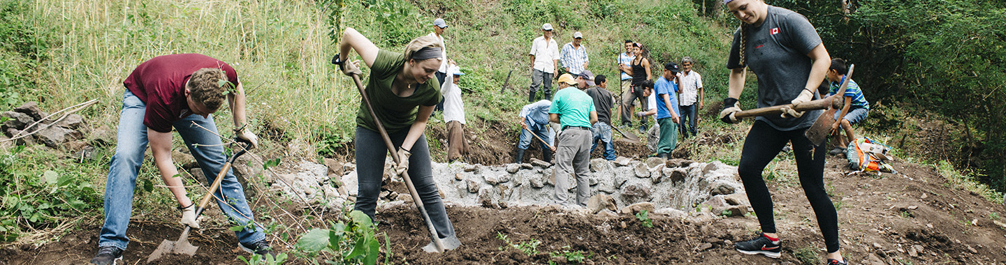 students digging during service learning experience