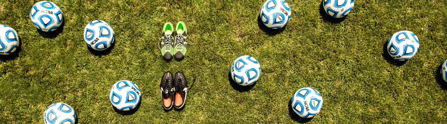 soccer balls and shoes on grass