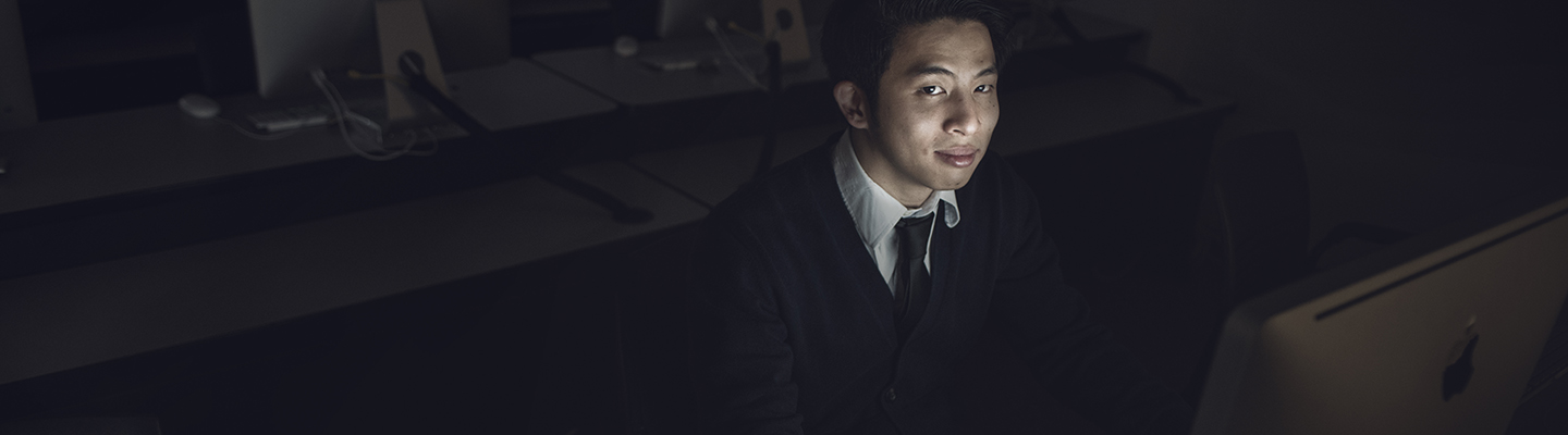 student in dark room on computer
