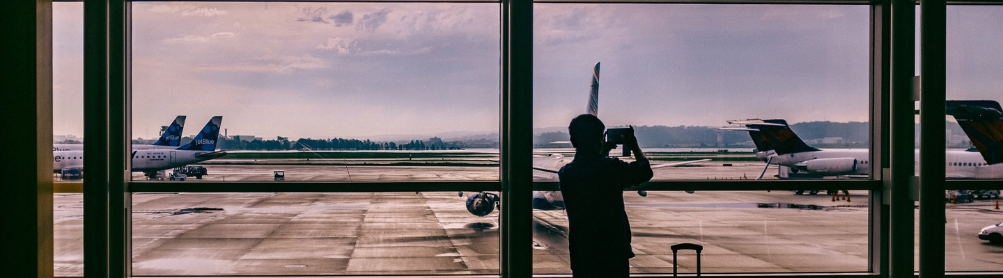 traveller takes photo of planes from inside airport