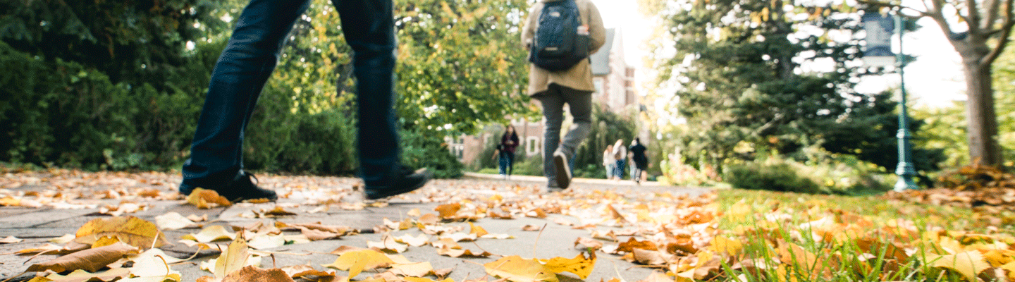 two students feet walking on fall leaves