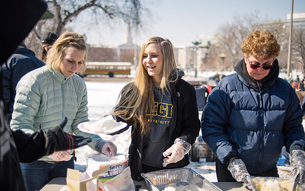 Student and faculty handing out food to people in need