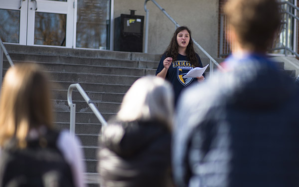 girl addressing a crowd on the library steps