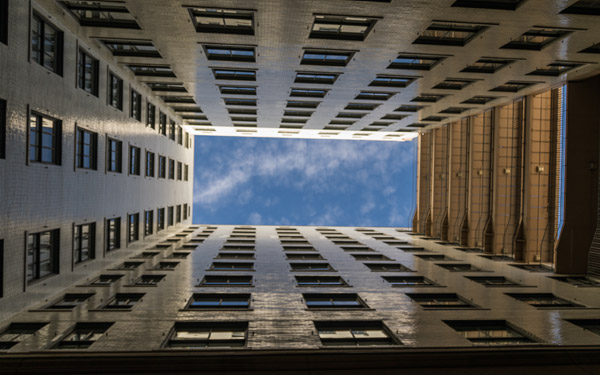 courtyard with building windows, sky peeks through