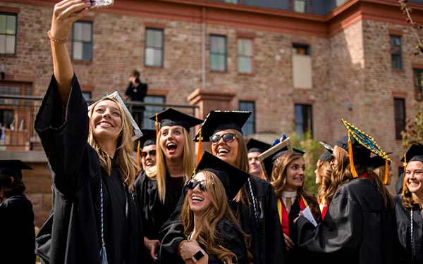 graduates take selfie at commencement