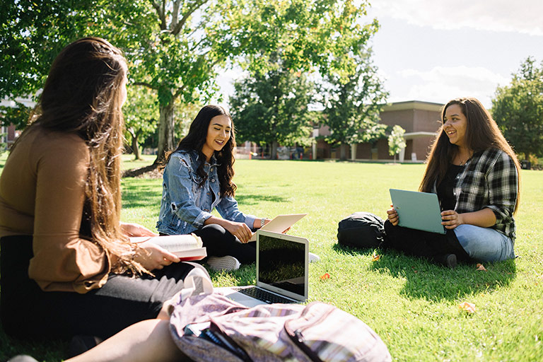 freshmen students sit in a grassy area on campus