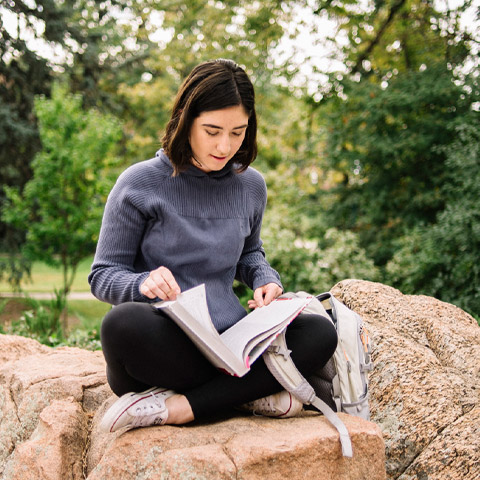 girl sits on rock and reads textbook