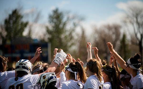 women's lacrosse team huddles on the field