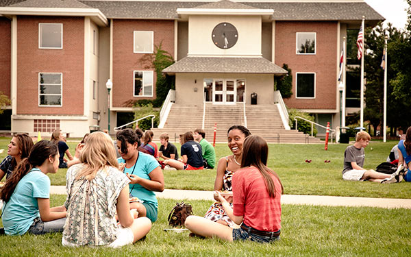students sitting on quad in front of library