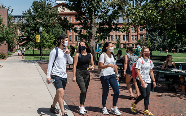 Masked students walk on campus