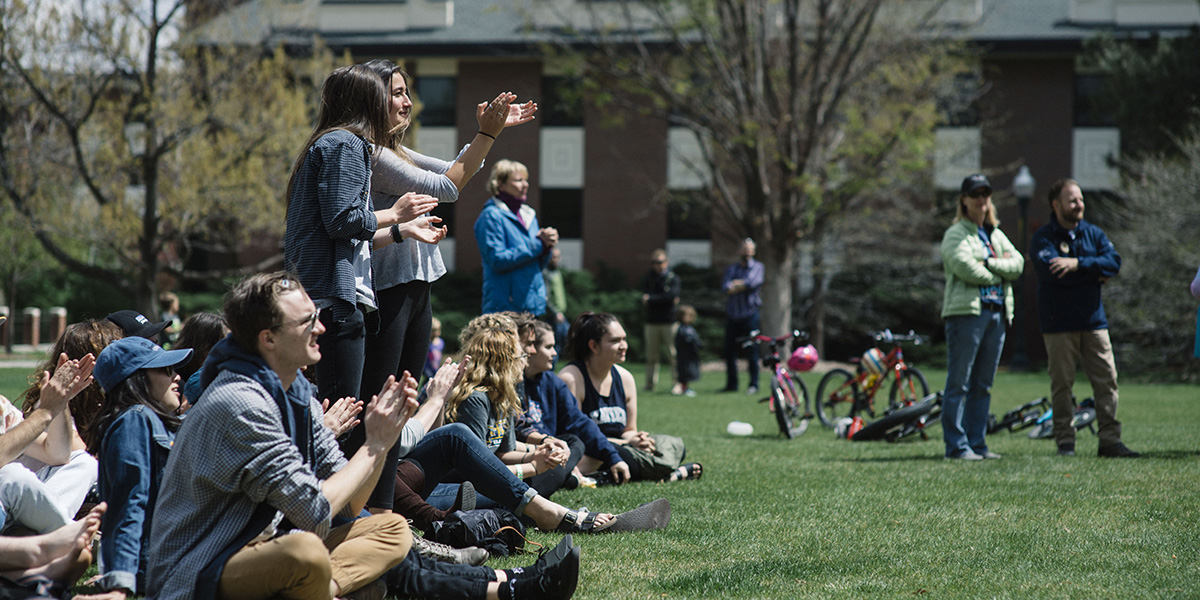 students sitting and clapping on the quad
