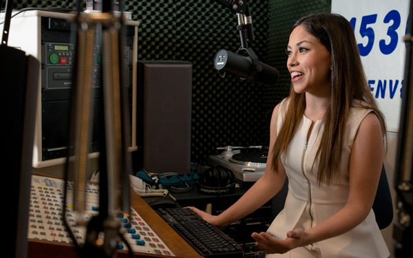 student speaking into mic in sound booth for podcast