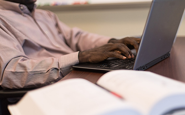 closeup of a mans hands at a computer with an open textbook
