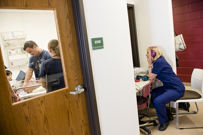 professor observing nursing students through window