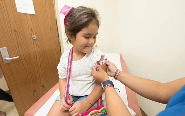 person wearing scrubs applies a bandage to smiling child's arm