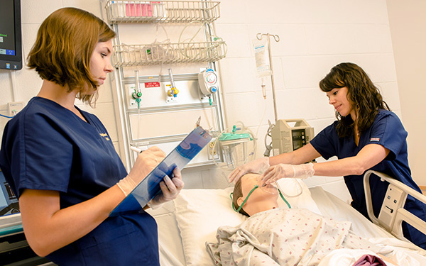 two nurses attend to a medical mannequin