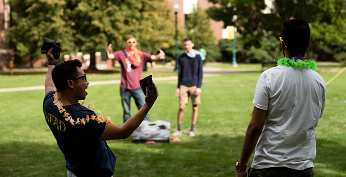 Student celebrate during a game of hacky sack