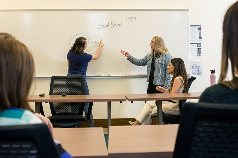 two students debate in a classroom