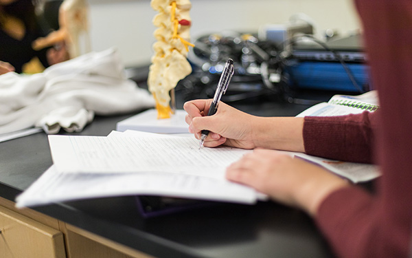 student takes notes in a science classroom