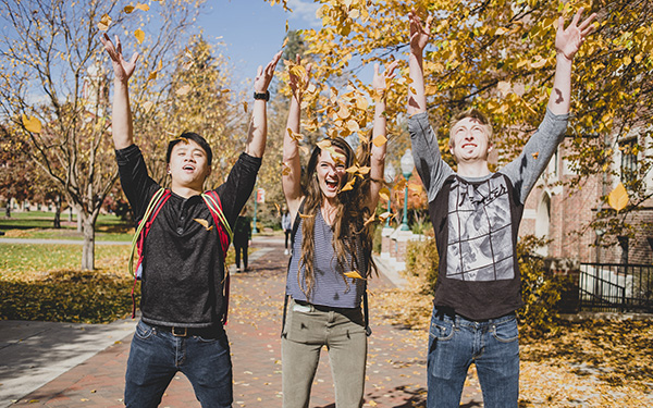 students throw leaves in air in fall