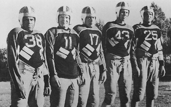 Walter Springs and 4 other men stand in a line wearing 1940s football uniforms