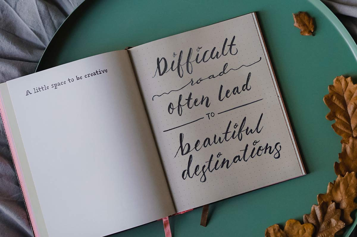 """Open notebook with handwritten quote: """"Difficult roads often lead to beautiful destinations"""""""