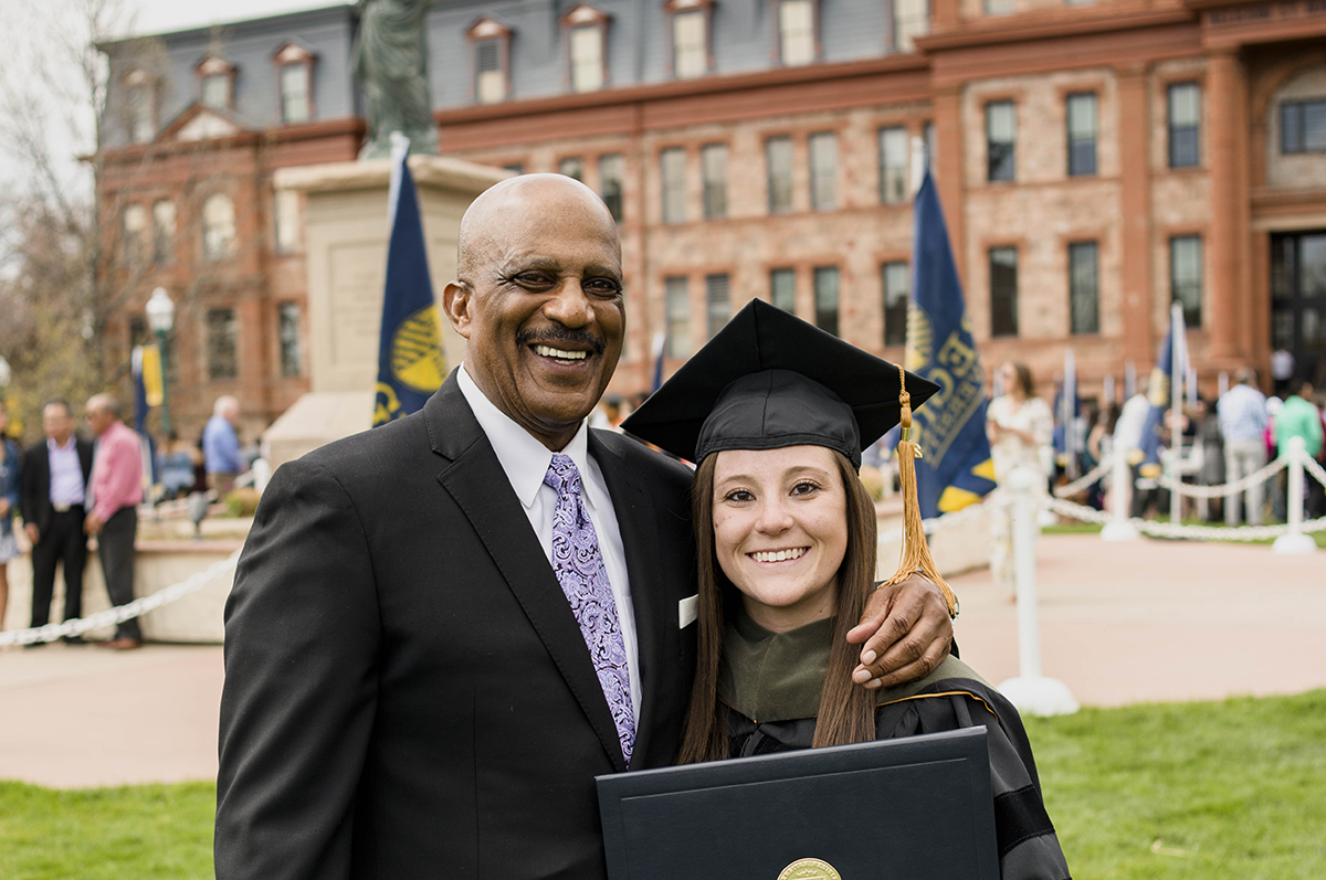 Lonnie Porter and Monique Gonzales pause for a picture after Monique received her doctorate from Regis