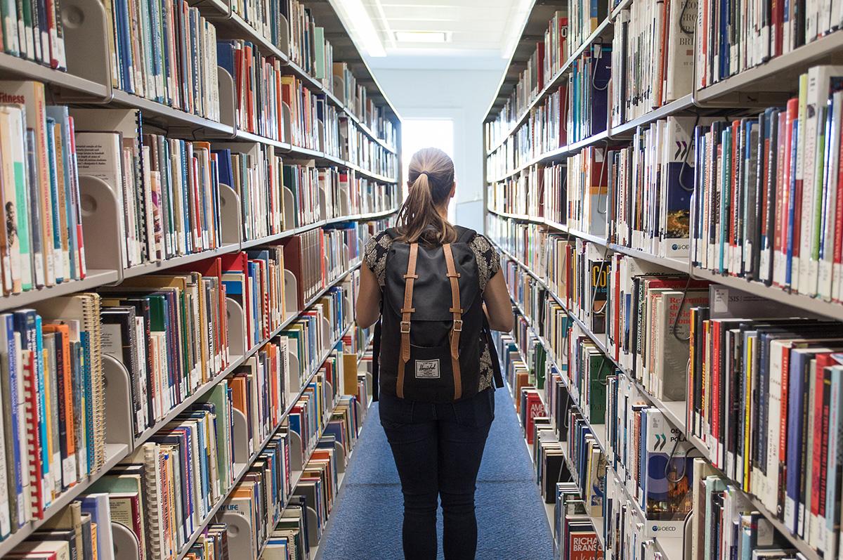 Student walks through book shelves in Regis University's Dayton Memorial Library