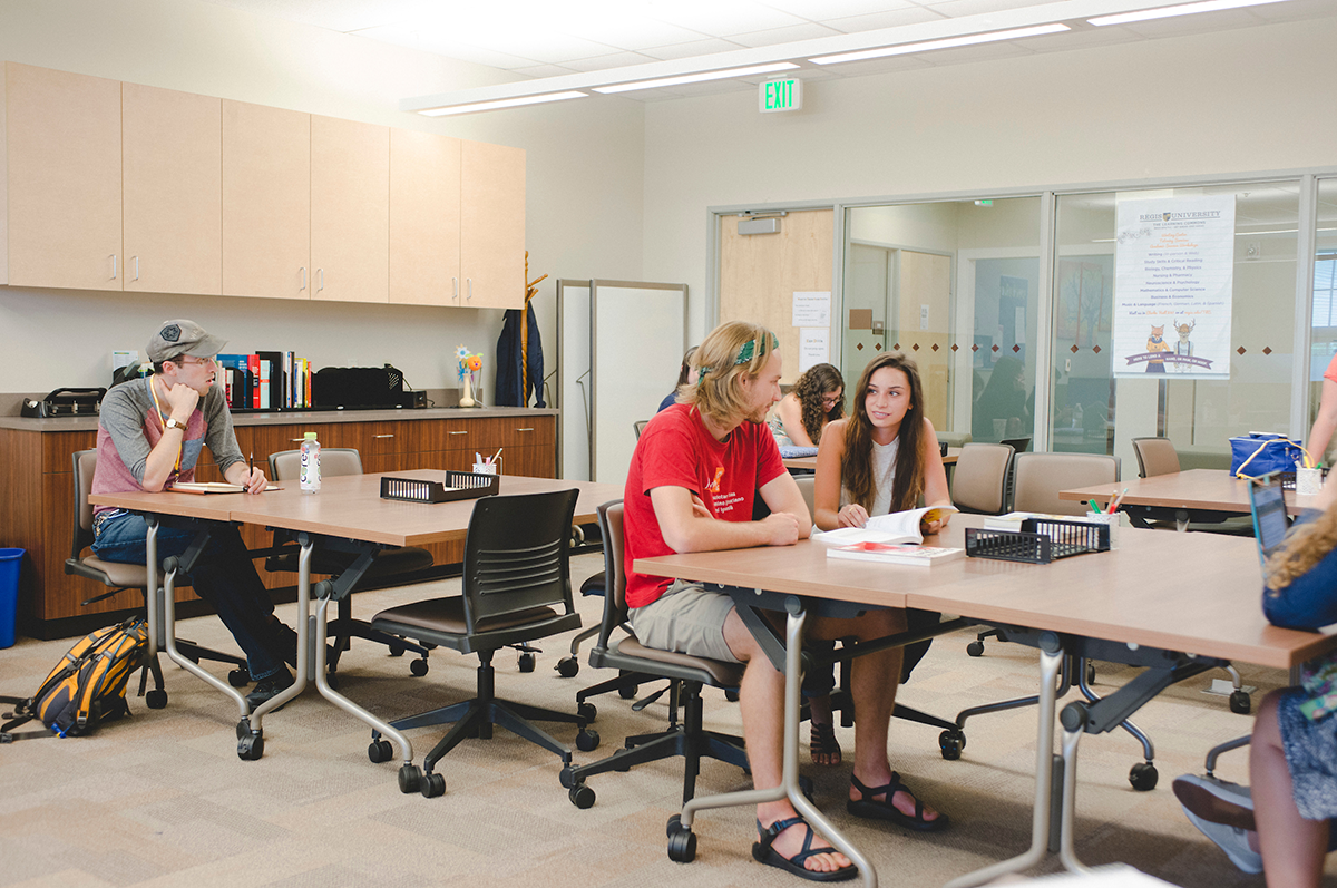 A student works with a tutor to complete an assignment in The Learning Commons at Regis University.