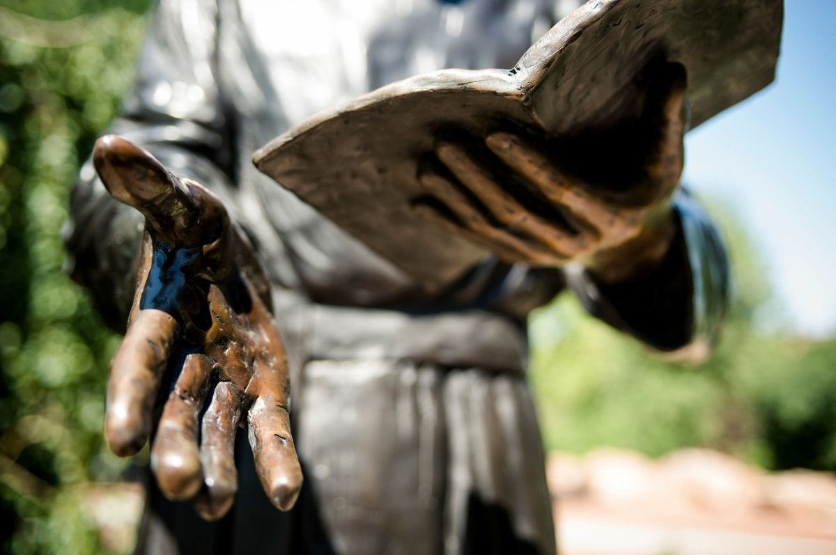statue hands holding book