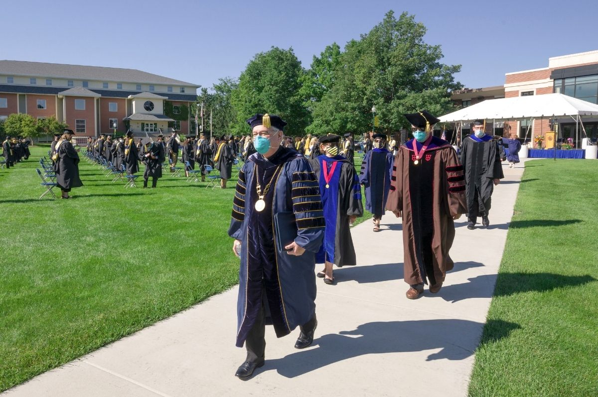 people wearing commencement attire and masks