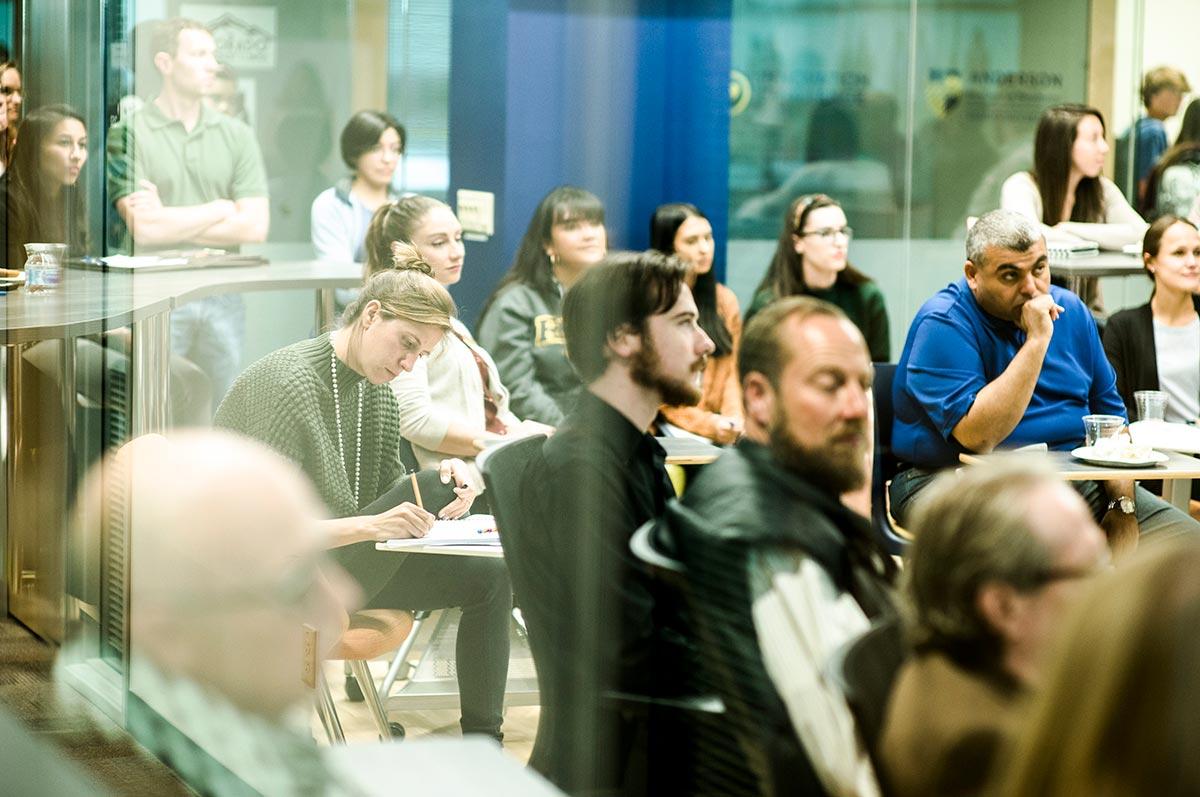 people sit at desks at the Innovation Challenge