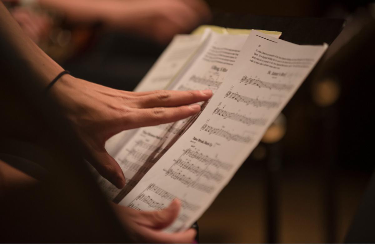A member of Regis University's music program adjusts sheet music