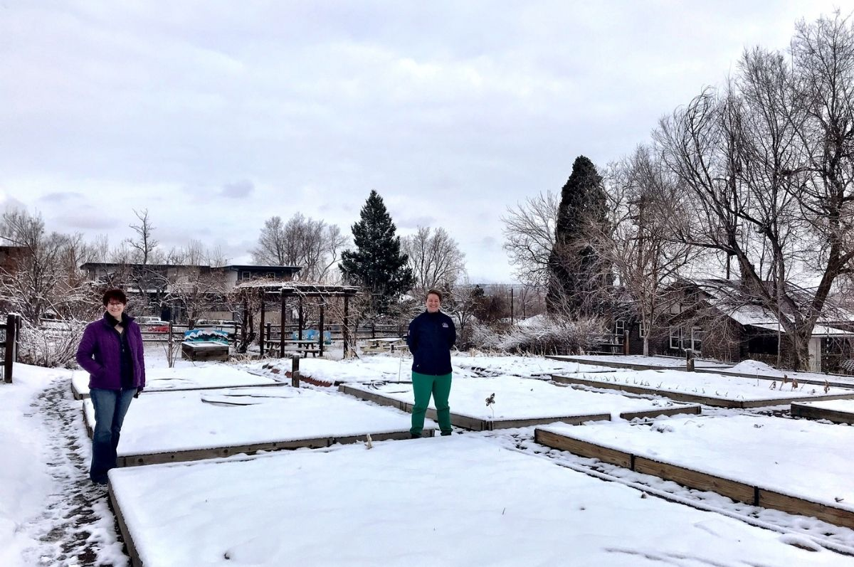 women standing in snowy garden