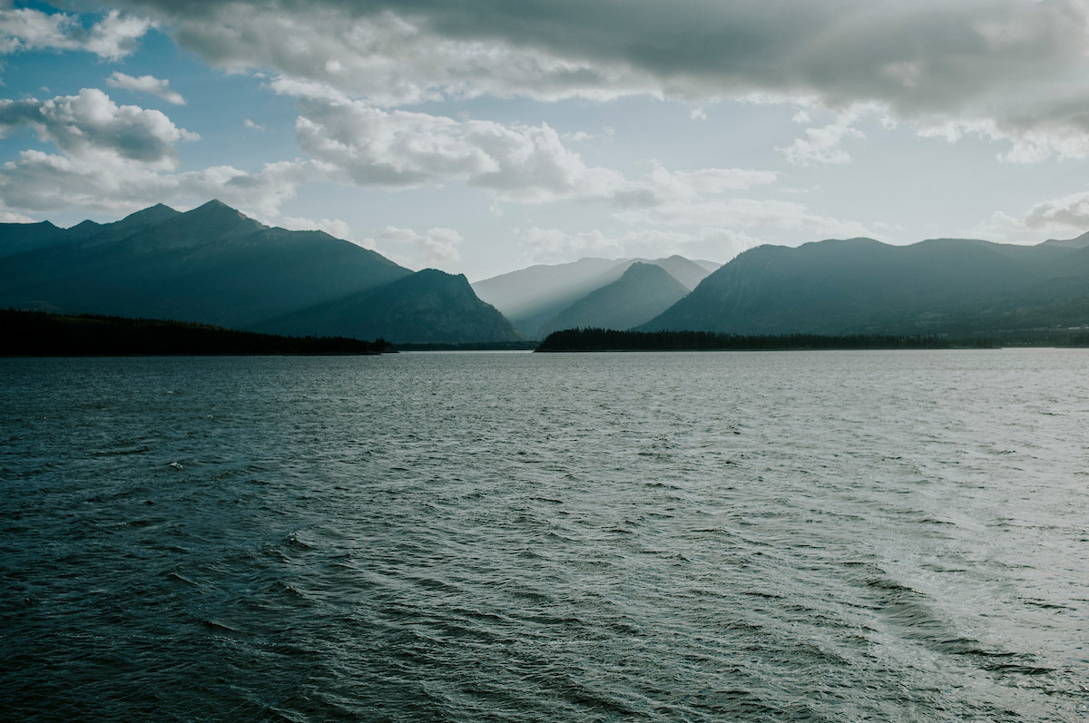 a rain storm sits on top of mountains across a lake during a Regis University Outdoor Adventure Program trip