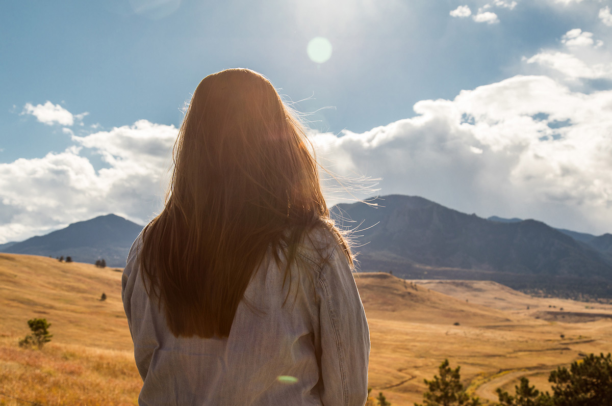 woman seen from behind stands in front of mountains in the sunshine